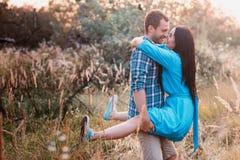 Le jeune homme porte dedans ses bras une jeune fille attirante en parc Photo stock
