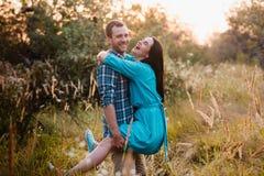 Le jeune homme porte dedans ses bras une jeune fille attirante en parc Photos libres de droits