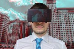 Le jeune homme porte des lunettes de réalité virtuelle simulation 3D de ville Images libres de droits