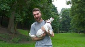 Le jeune homme positif avec une barbe tient son chien aimé Jack Russell Terrier et apprécie un repos commun dans la cour clips vidéos
