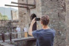 Le jeune homme prend une photo d'un château photo stock