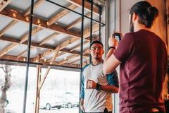 Le jeune homme prend une photo de son ami arabe Amis de métis passant le temps en café Images stock