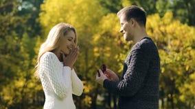 Le jeune homme propose à l'amie avec l'anneau, engagement en parc d'automne, amour photos stock