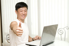 Le jeune homme réussi avec l'ordinateur s'assied Images libres de droits