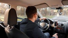 Le jeune homme réussi conduit une voiture un jour ensoleillé photographie stock