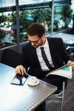 Le jeune homme réussi s'asseyant sur la terrasse d'un restaurant et fait des plans pour le jour Photographie stock libre de droits