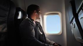 Le jeune homme regarde la fenêtre de l'avion le soir Il écoute les écouteurs et les repos banque de vidéos