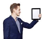 Le jeune homme regarde le comprimé numérique Image libre de droits