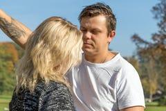 Le jeune homme regarde sérieusement la femme blonde Photo libre de droits