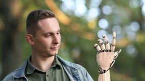 Le jeune homme regarde sur sa main robotique en parc belle animation 3d réaliste 4K banque de vidéos
