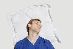 Le jeune homme a reposé sa tête sur l'oreiller au-dessus du fond coloré Image libre de droits