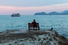 Le jeune homme repose seul au bord de la mer au crépuscule rêve photographie stock