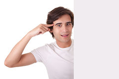 Le jeune homme retenant un panneau-réclame blanc, faisant des gestes ont Photographie stock