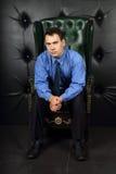 Le jeune homme sérieux dans le bleu s'assied dans le fauteuil en cuir Images libres de droits