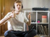 Le jeune homme s'asseyant à la maison écoutent musique dans des écouteurs avec le pouce  photographie stock libre de droits