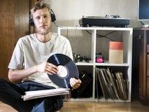 Le jeune homme s'asseyant dans le salon confortable tenant le disque de disque vinyle près enregistre le support sur le plancher images stock