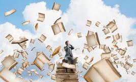 Le jeune homme s'asseyant sur des livres et ne veulent voir rien Image stock