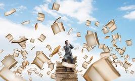 Le jeune homme s'asseyant sur des livres et ne veulent voir rien Photographie stock