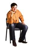 Le jeune homme s'asseyant sur une présidence affiche le doigt Image libre de droits