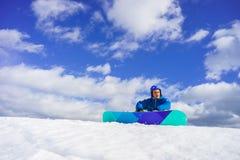 Le jeune homme s'asseyent sur la neige Photographie stock libre de droits