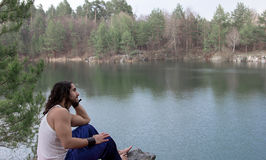 Le jeune homme s'assied sur la berge détendez Photographie stock