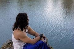 Le jeune homme s'assied sur le lac et observe la nature Images libres de droits