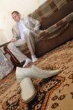 Le jeune homme s'assied sur un sofa Photographie stock libre de droits