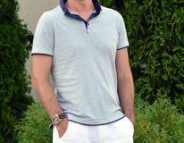 Le jeune homme sûr en chemise et été blanc halète la pose Photographie stock