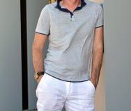 Le jeune homme sûr en chemise et été blanc halète la pose près du mur de briques Photos libres de droits
