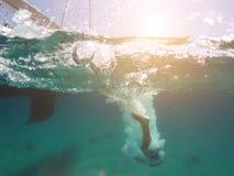 Le jeune homme sautant d'un yacht dans la mer Photo sous-marine photo libre de droits