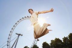 Le jeune homme sautant en Front Of London Eye Photos stock