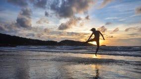 Le jeune homme sautant sur la plage quand coucher du soleil Photo stock