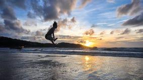 Le jeune homme sautant sur la plage quand coucher du soleil Image stock