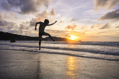 Le jeune homme sautant sur la plage quand coucher du soleil Photographie stock libre de droits