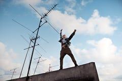 Le jeune homme sautant sur le dessus de toit avec le ciel bleu lumineux et les nuages blancs au fond images libres de droits