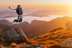 Le jeune homme sautant sur une montagne contre le ciel image stock