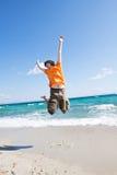 Le jeune homme saute à la mer Photographie stock