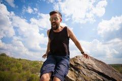 Le jeune homme saute du haut de la roche Photo libre de droits