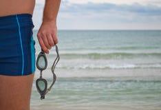 Le jeune homme se tient contre les prises d'horizon de l'eau de vagues de sable de plage de bord de mer dans des ses lunettes de  photos stock