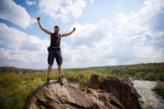 Le jeune homme se tient sur le dessus de la roche Photos stock