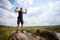 Le jeune homme se tient sur le dessus de la roche Photos libres de droits