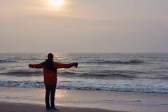 Le jeune homme se tient sur le rivage de la Mer du Nord et examine la distance photos stock