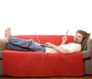 Le jeune homme se trouve sur le sofa photographie stock