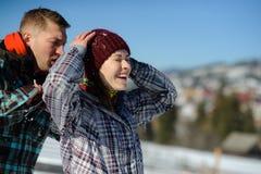 Le jeune homme secoue soigneusement la neige des vêtements d'amie Photo stock