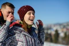 Le jeune homme secoue soigneusement la neige des vêtements d'amie Photos stock