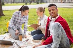 Le jeune homme souriant tout en aidant ses amis avec l'étudiant projettent Photos libres de droits