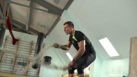 Le jeune homme sportif est engag? dans des cordes dans le gymnase banque de vidéos