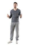 Le jeune homme sportif heureux d'ajustement montrant des pouces lèvent le geste souriant à l'appareil-photo Photo libre de droits