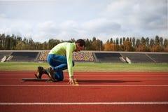 Le jeune homme sportif sont prêt à fonctionner sur le champ de courses au grand stade moderne gentil Images stock