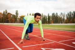 Le jeune homme sportif sont prêt à fonctionner sur le champ de courses Personnes bien formées convenables au grand stade moderne  Photo stock